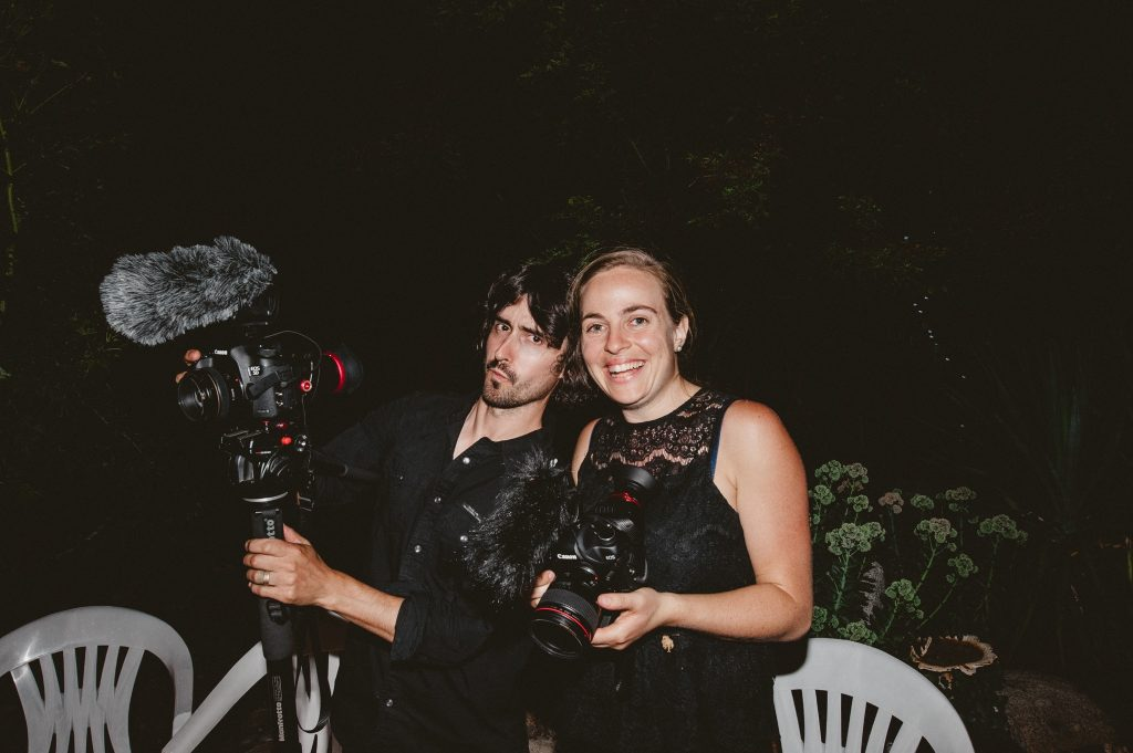 Melissa and Jim with their cameras filming a wedding video.