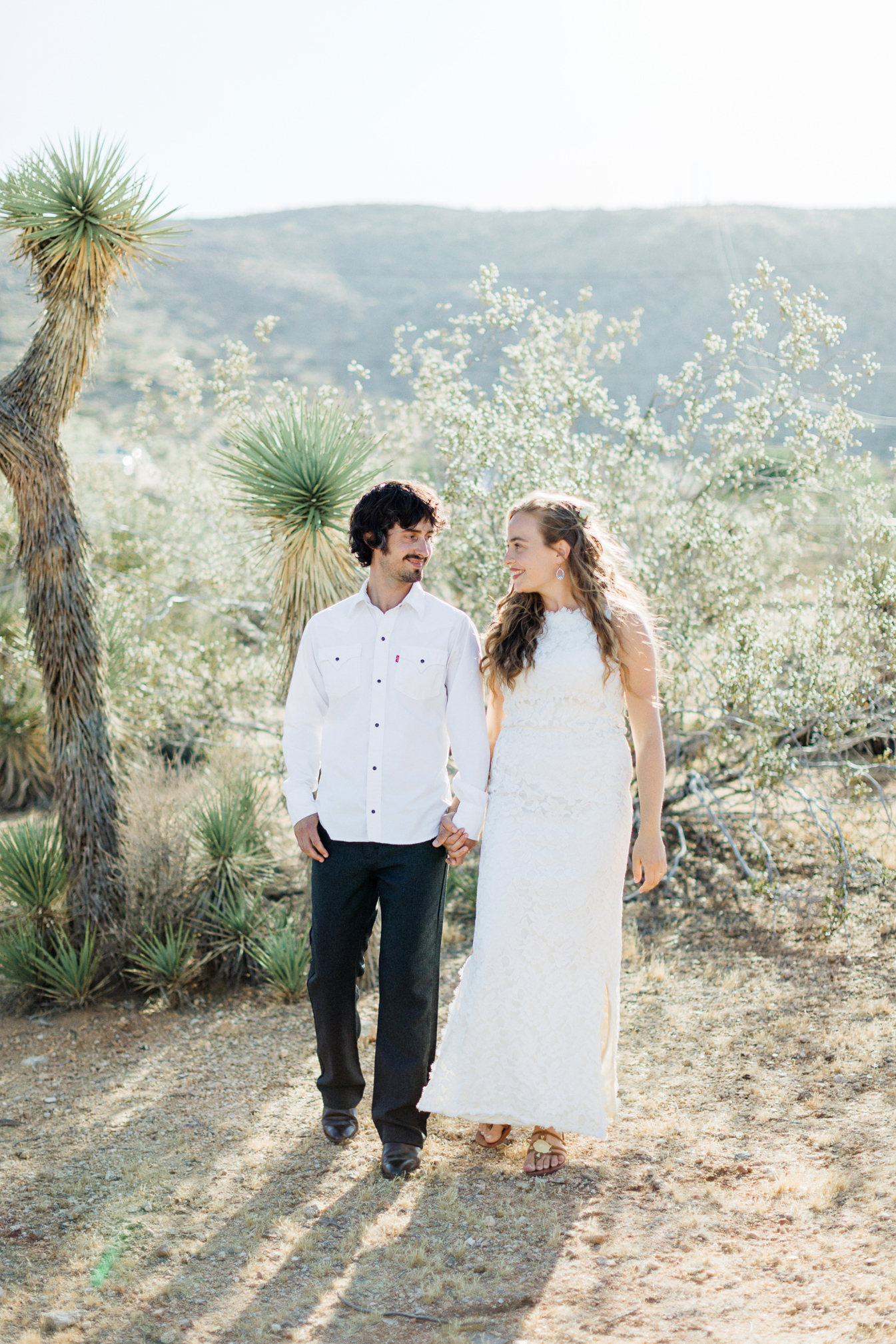 Jim and Melissa dressed for their wedding standing by a Joshua Tree