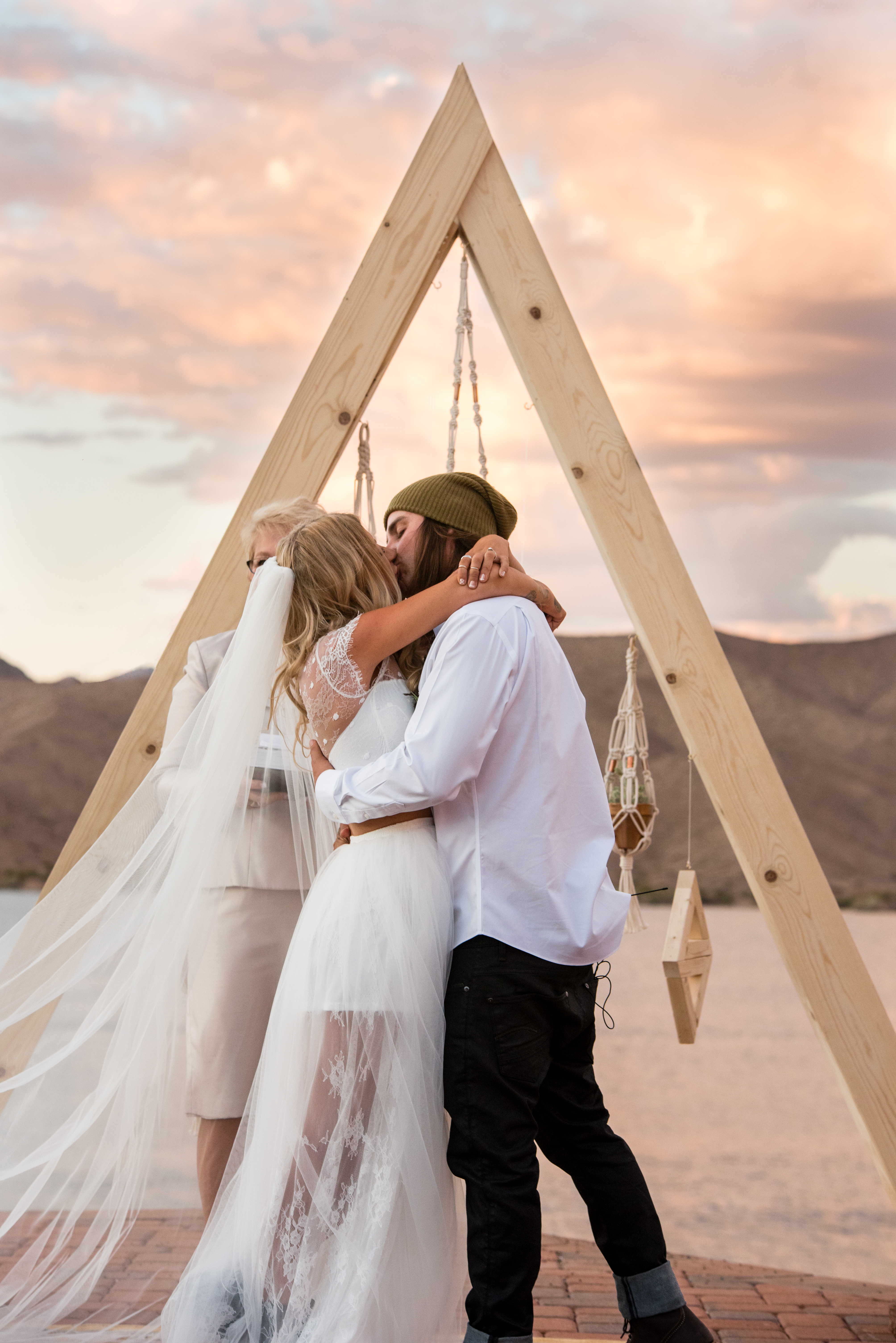 Couple kissing during a sunset wedding ceremony by Lake Havasu
