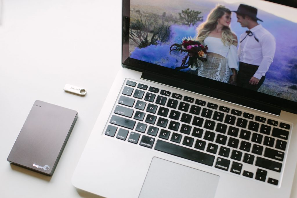 Photo of a wedding video on a laptop with an external hard drive and flash drive.